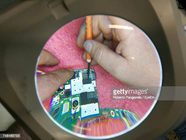 Cropped Hands Of Male Technician Repairing Chip Seen Through Magnifying Glass