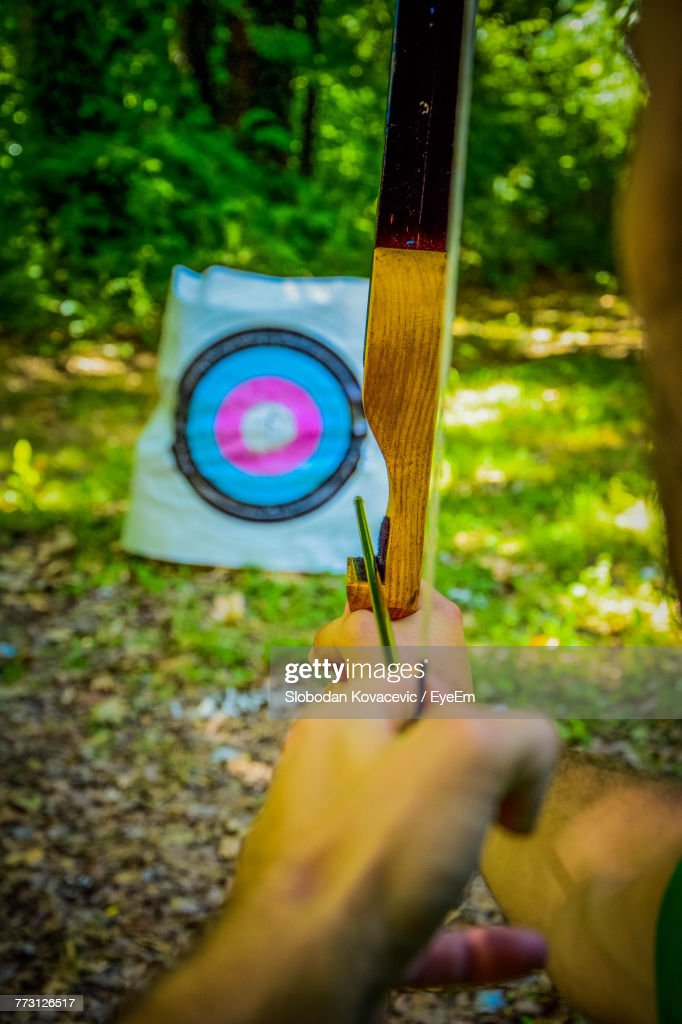 Cropped Hands Of Man Aiming Bow And Arrow : Photo