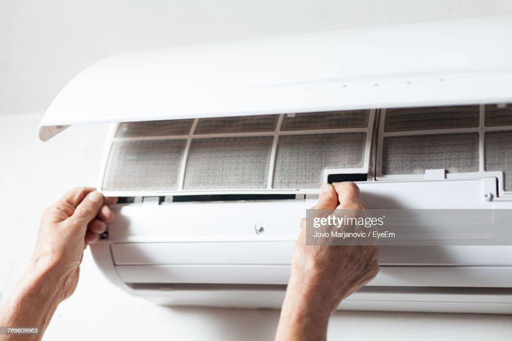 Cropped Hands Of Man Cleaning Air Conditioner On Wall : Stock Photo