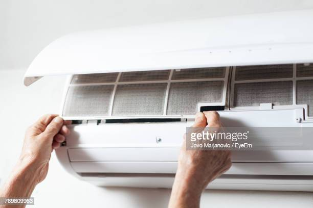 Cropped Hands Of Man Cleaning Air Conditioner On Wall