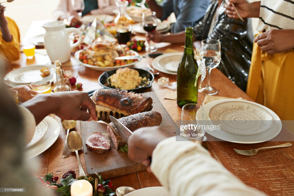 Cropped hands of man cutting meat on dining table : Stockfoto