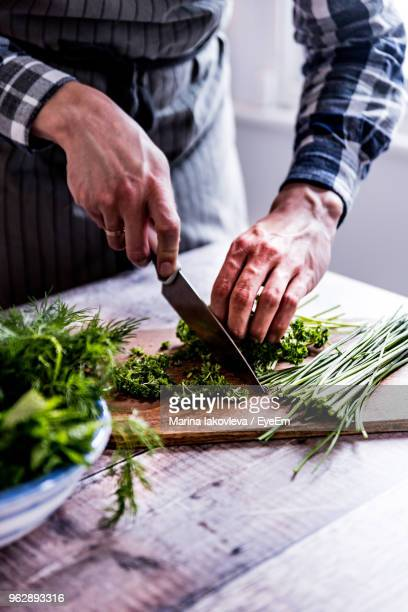 cropped hands of man cutting vegetables on table - chop stock pictures, royalty-free photos & images