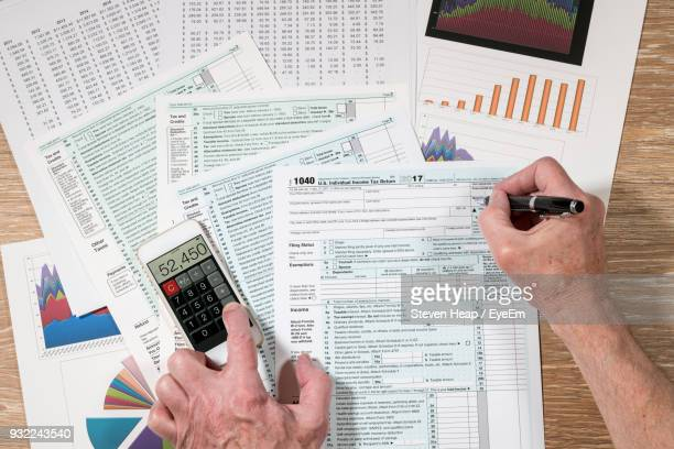 Cropped Hands Of Man Doing Paperwork On Table