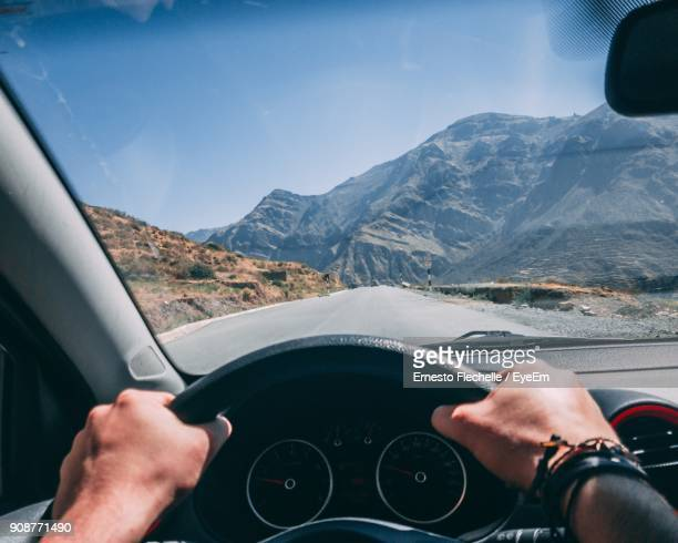 Cropped Hands Of Man Driving Car On Road Against Sky