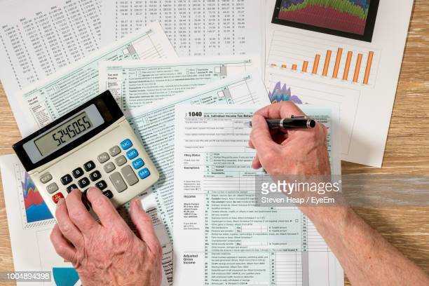 cropped hands of man filing documents using calculator at table - filing documents stock pictures, royalty-free photos & images