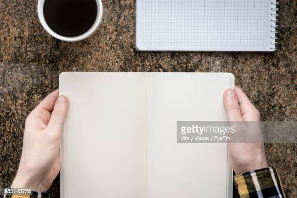 cropped hands of man holding blank diary over table - one man only stock pictures, royalty-free photos & images