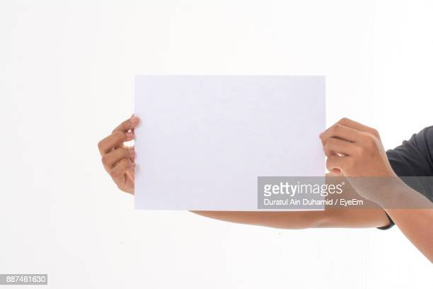 Cropped Hands Of Man Holding Blank Paper Against White Background