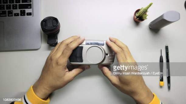 Cropped Hands Of Man Holding Camera At Table