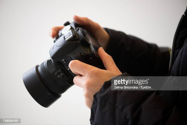 Cropped Hands Of Man Holding Camera