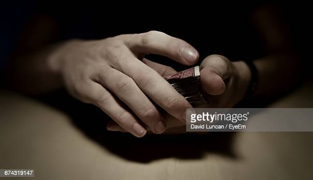 Cropped Hands Of Man Holding Cards On Table