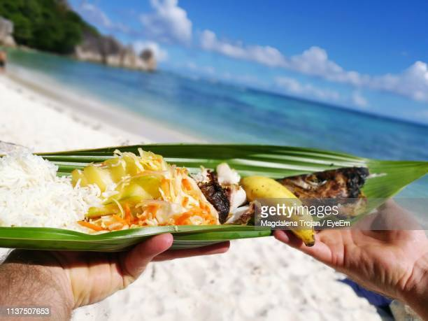 cropped hands of man holding food in leaf at beach - seychelles stock pictures, royalty-free photos & images