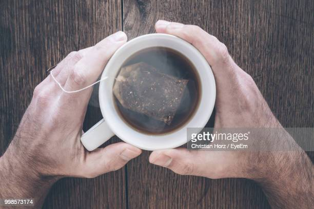 cropped hands of man holding hot tea cup on wooden table - tea hot drink stock pictures, royalty-free photos & images