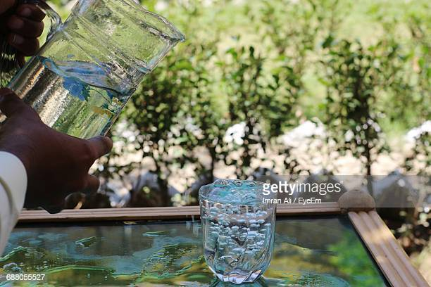 Cropped Hands Of Man Holding Pitcher By Glass With Water On Table