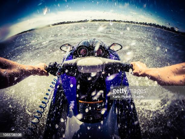 cropped hands of man jet boating in sea - jet ski stock pictures, royalty-free photos & images