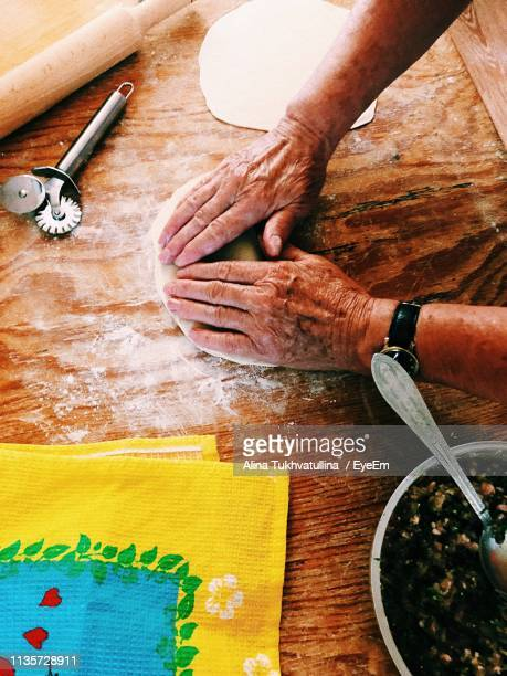Cropped Hands Of Man Kneading Dough On Wooden Table