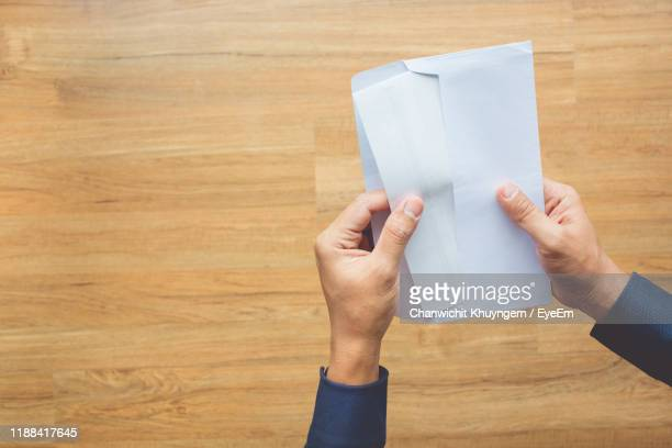 cropped hands of man opening envelope at table - 封筒 ストックフォトと画像