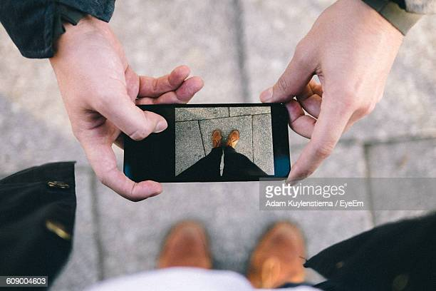 Cropped Hands Of Man Photographing Person Legs