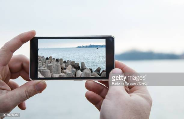 Cropped Hands Of Man Photographing Sea With Mobile Phone