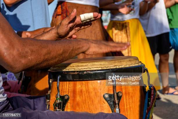 cropped hands of man playing drum outdoors - samba stock pictures, royalty-free photos & images