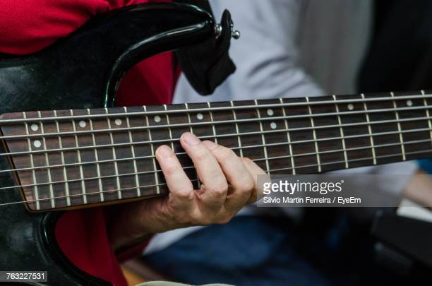 cropped hands of man playing guitar - martin guitar stock photos and pictures