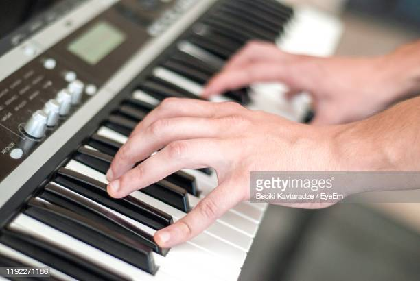 cropped hands of man playing piano - キーボード奏者 ストックフォトと画像