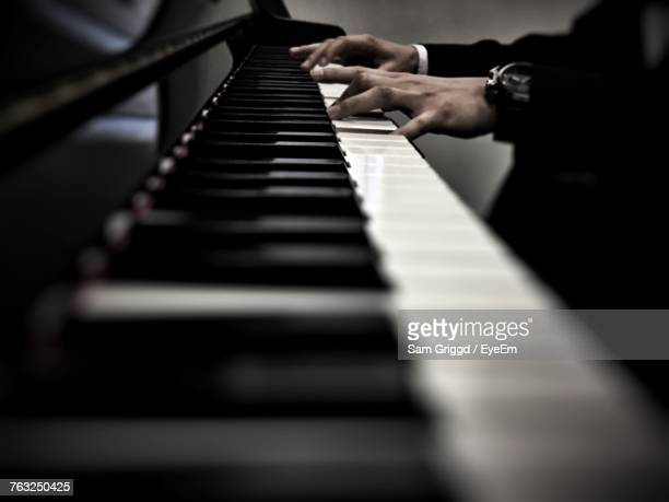cropped hands of man playing piano - piano key stock photos and pictures