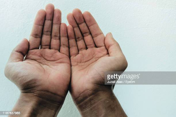 cropped hands of man praying against white wall - hands cupped stock pictures, royalty-free photos & images