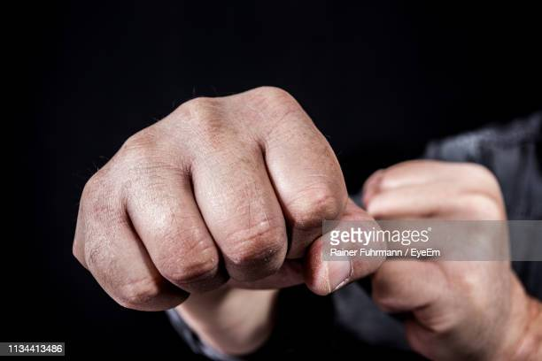 cropped hands of man punching over black background - punching stock pictures, royalty-free photos & images