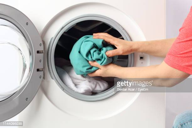 cropped hands of man putting clothes in washing machine at home - laundry stock pictures, royalty-free photos & images
