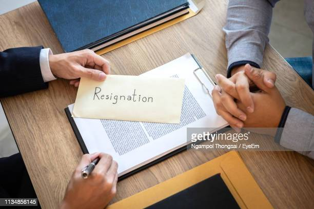cropped hands of man receiving resignation letter from employee at office - quitting a job stock pictures, royalty-free photos & images