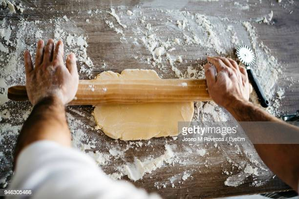 Cropped Hands Of Man Rolling Dough On Table In Kitchen