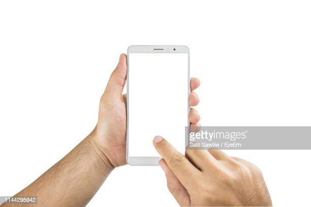 cropped hands of man using smart phone against white background - finger stock pictures, royalty-free photos & images
