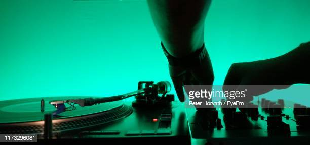cropped hands of man using sound mixer by turntable - クラブdj ストックフォトと画像
