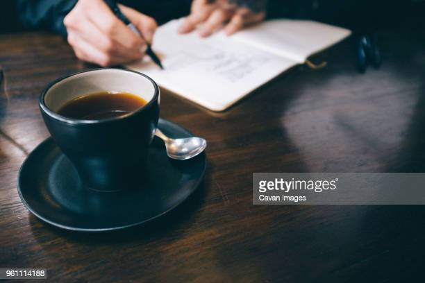 cropped hands of man writing with black coffee served on table - 人体部位 ストックフォトと画像