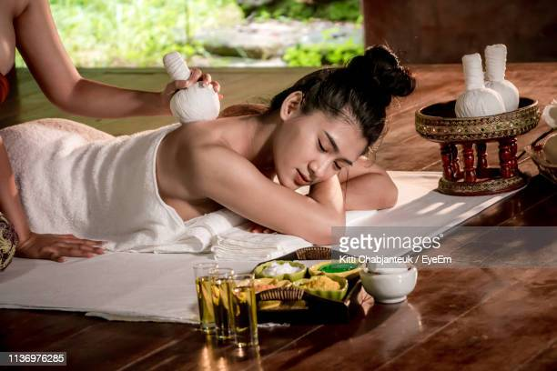 cropped hands of massage therapist massaging female customer in spa - thai massage stock photos and pictures