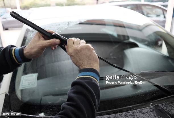 cropped hands of mechanic holding windshield wiper against car at auto repair shop - windshield wiper stock photos and pictures