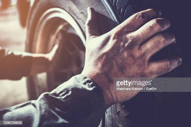 cropped hands of mechanic repairing engine in workshop - werkstatt stock-fotos und bilder