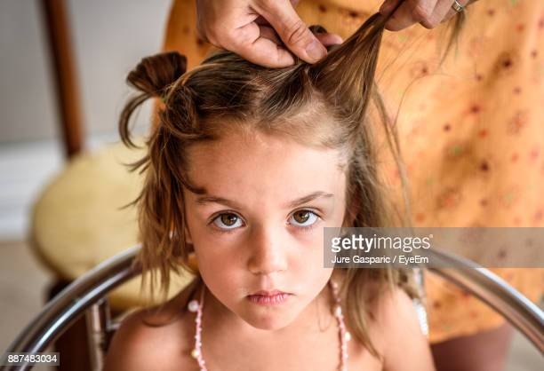 Cropped Hands Of Mother Braiding Daughter Hair