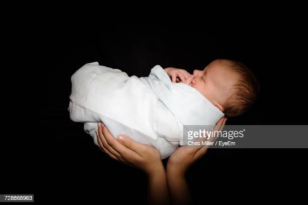 cropped hands of parent holding newborn baby against black background - cute black newborn babies stock photos and pictures