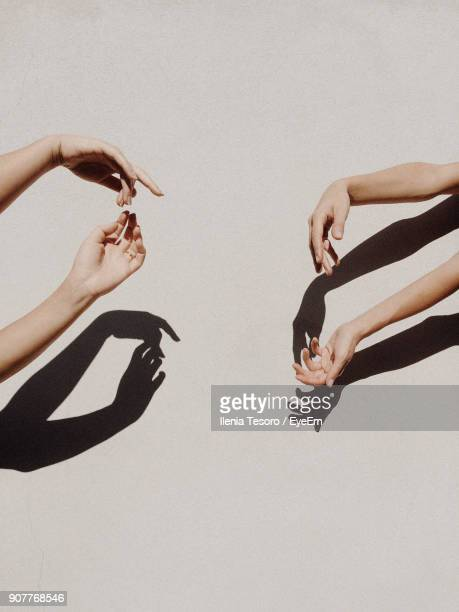 cropped hands of people gesturing against gray wall - ombra in primo piano foto e immagini stock