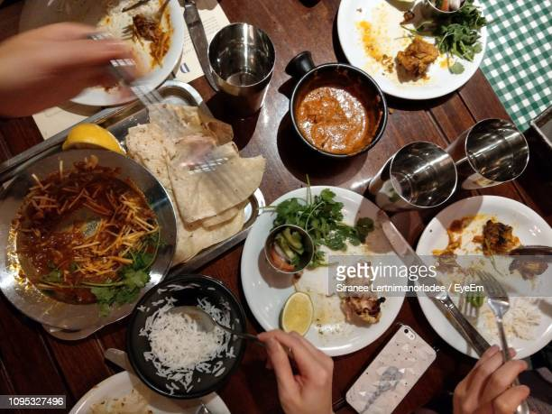 cropped hands of people having food at dining table in restaurant - indian food stock pictures, royalty-free photos & images