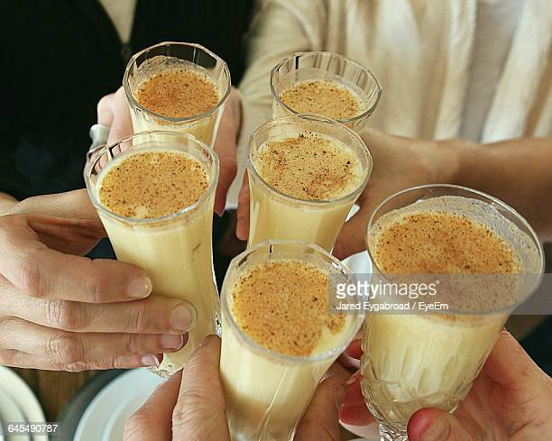 cropped hands of people holding eggnog - eggnog stock photos and pictures