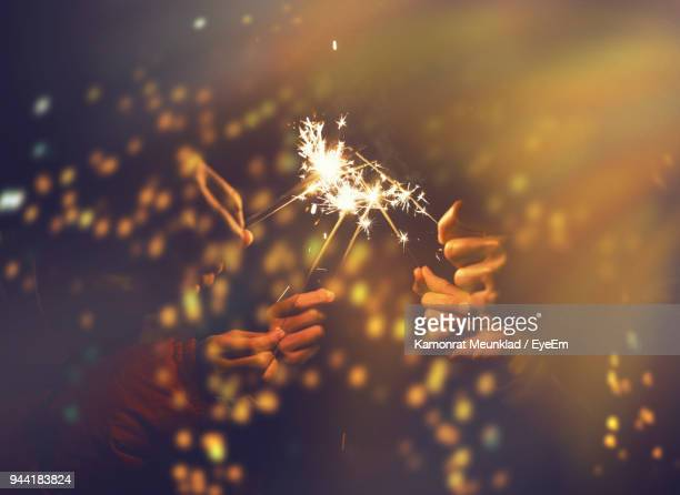 Cropped Hands Of People Holding Sparkler At Night