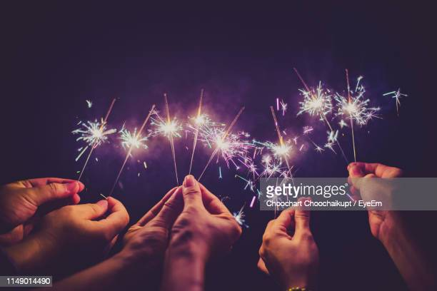 cropped hands of people holding sparklers at night - sparkler stock pictures, royalty-free photos & images