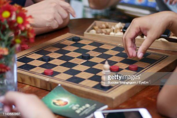 cropped hands of people playing board game on table - chequers stock pictures, royalty-free photos & images