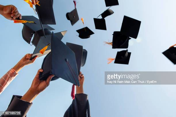 cropped hands of people throwing mortarboards against clear sky - graduation stock pictures, royalty-free photos & images