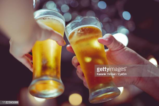 cropped hands of people toasting beer glasses in bar - honour stock pictures, royalty-free photos & images