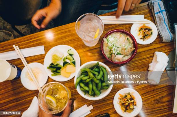 Cropped Hands Of People With Food And Drink On Wooden Table