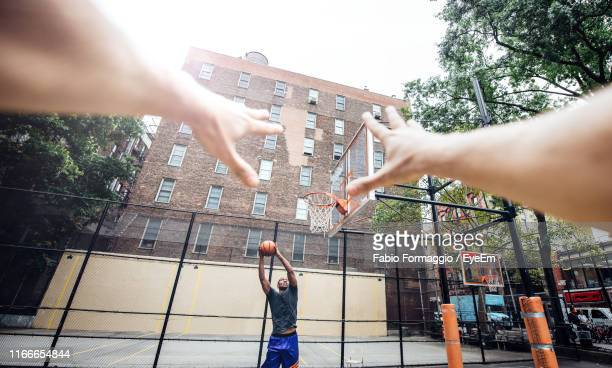cropped hands of person against man playing basketball at court - personal perspective stock pictures, royalty-free photos & images