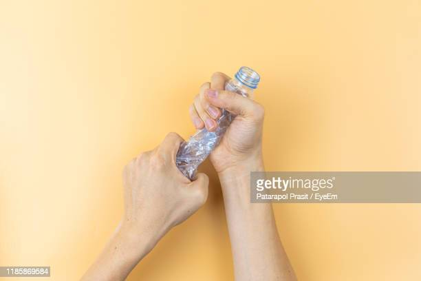 cropped hands of person crushing bottle against yellow background - crush foto e immagini stock